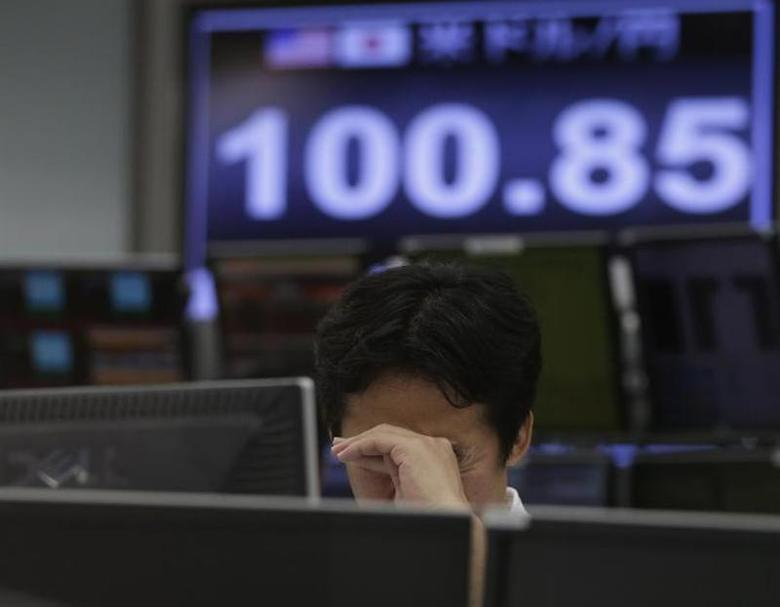 An employee at a foreign exchange trading company reacts in front of monitors displaying the Japanese yen's exchange rate against the U.S. dollar in Tokyo May 10, 2013. REUTERS/Toru Hanai