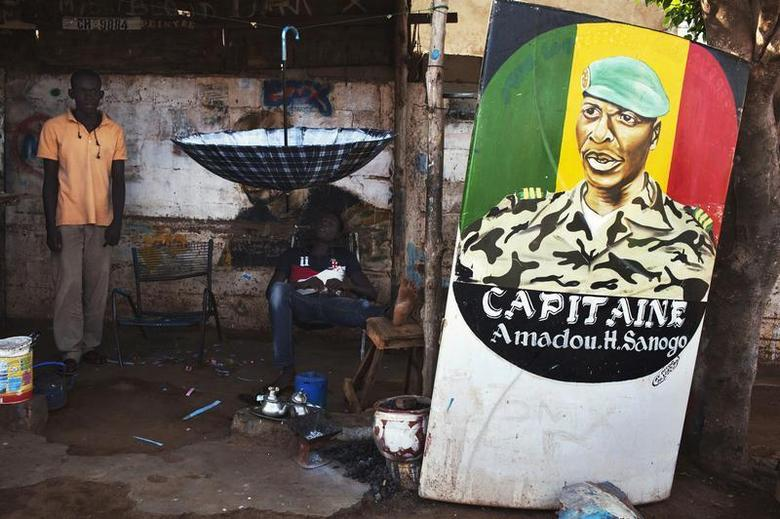 Men sit next to a painting of the ex-junta leader Amadou Haya Sanogo in Bamako July 16, 2013. Mali will be holding presidential election on July 28. The poster reads, REUTERS/Joe Penney