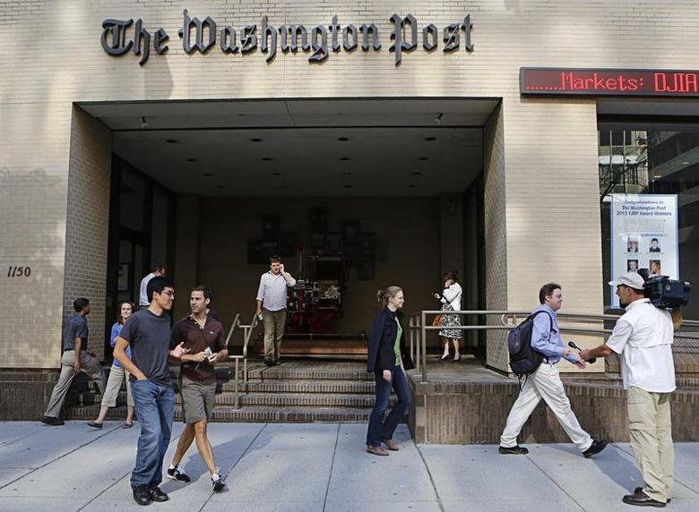 A television cameraman takes up a position as people walk by the entrance of the Washington Post headquarters in Washington, August 5, 2013. REUTERS/Stelios Varias