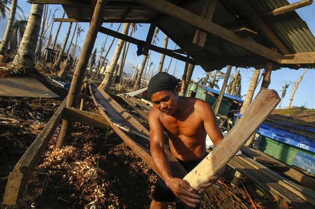 Roy, 43, who lost his two fishing boats during Typhoon Haiyan, builds his new fishing boat in the ruins of a destroyed neighborhood at Tacloban City November 25, 2013. REUTERS/Athit Perawongmetha