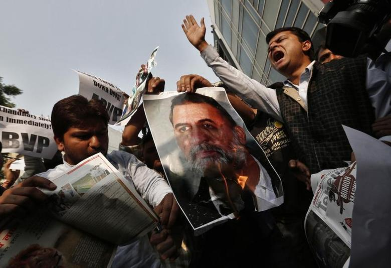 Activists of the Akhil Bharatiya Vidyarthi Parishad (ABVP), linked to India's main opposition Bharatiya Janata Party (BJP), burn a poster of Tarun Tejpal, editor-in-chief of India's leading investigative magazine, during a protest in New Delhi November 22, 2013. REUTERS/Adnan Abidi