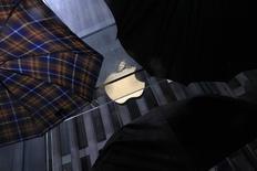 Люди с зонтами у магазина Apple в Нью-Йорке 19 мая 2013 года. Окружной суд Калифорнии отклонил в среду потребительский иск к Apple Inc о нарушении конфиденциальности данных, не увидев достаточных доказательств того, что на истцов как-то влияли действия компании и они могли от них пострадать. REUTERS/Eric Thayer
