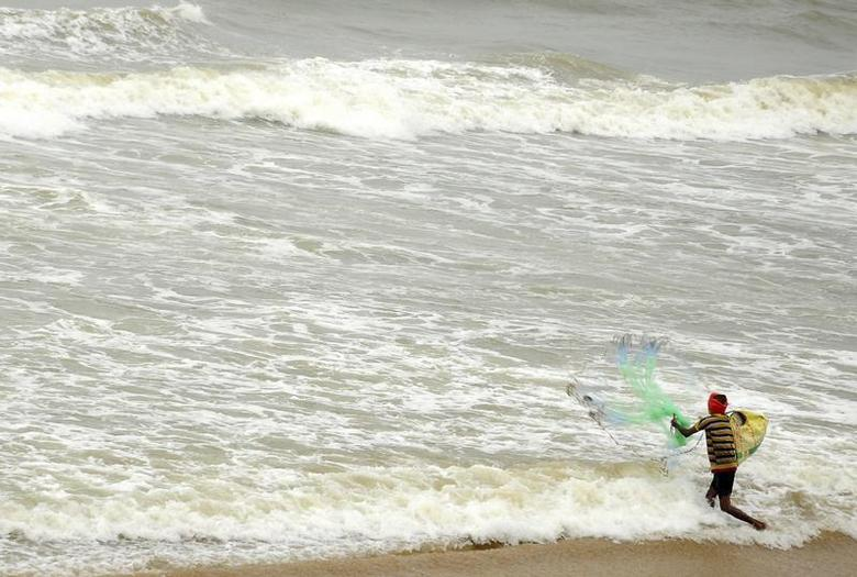 A fisherman casts his net to catch fish in the waters of the Bay of Bengal in Visakhapatnam district in the southern Indian state of Andhra Pradesh November 28, 2013. REUTERS/R Narendra