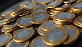Moedas de um real são fotografas no Rio de Janeiro. A inadimplência no mercado de crédito brasileiro no segmento de recursos livres ficou em 5 por cento em outubro, abaixo da taxa de setembro, quando registrou 5,1 por cento, informou nesta quarta-feira o Banco Central. 15/10/2010. REUTERS/Bruno Domingos