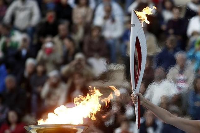Greek actress Ino Menegaki, playing the role of high priestess, raises an Olympic torch of the Sochi 2014 Winter Games during a handover ceremony at the Panathenean stadium in Athens October 5, 2013. REUTERS/Yorgos Karahalis