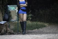 A prostitute waits for customers along a road of the Bois de Boulogne in Paris August 28, 2013. REUTERS/Christian Hartmann