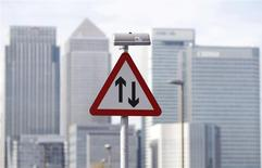 A traffic sign is pictured in front of the skyline of the the Canary Wharf financial district in London in this October 21, 2010 file photo. REUTERS/Luke Macgregor/Files