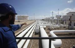Рабочий показывает на нефтепровод в порту и НПЗ в Эз-Завийя 22 августа 2013 года. Цены на нефть Brent держатся вблизи $111 за баррель на фоне продолжающихся беспорядков в Ливии и прогресса в решении вопроса о ядерной программе Ирана. REUTERS/Ismail Zitouny