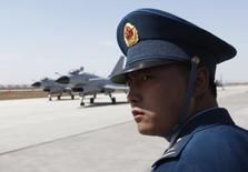 Военнослужащий ВВС Народно-освободительной армии Китая наблюдает за взлетом истребителей Чэнду J-10 на базе Янцунь 13 апреля 2010 года. Китайские власти направили истребители и самолеты дальнего обнаружения для патрулирования новой зоны противовоздушной обороны в Восточно-Китайском море, обострив противостояние с США, Японией и Южной Кореей. REUTERS/Petar Kujundzic
