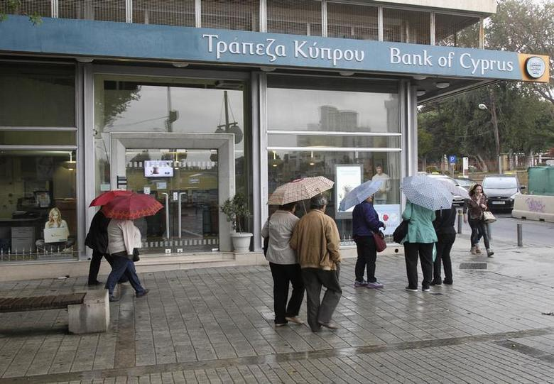 Cypriots walk outside a Bank of Cyprus branch on the island's capital Nicosia, April 18, 2013. REUTERS/Andreas Manolis