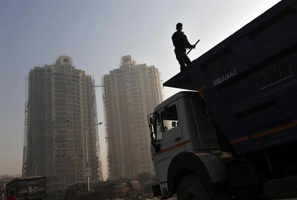 A labourer stands on a truck carrying construction materials at a construction site of residential buildings in Noida on the outskirts of New Delhi November 29, 2013. REUTERS/Adnan Abidi