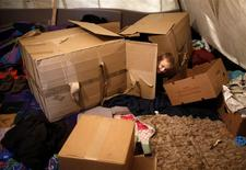 A Muslim Bosniak child plays amongst boxes in a camp in Sarajevo, November 19, 2013. REUTERS/Dado Ruvic