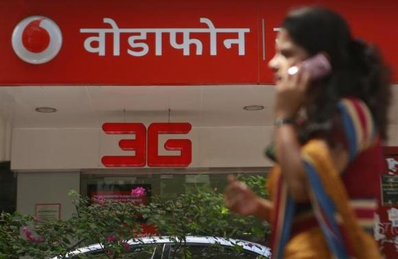 A woman talks on a mobile phone as she walks past a Vodafone store in Mumbai May 21, 2013. REUTERS/Danish Siddiqui/Files