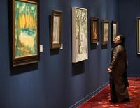 Visitante examina telas na prévia de um leilão de 'arte moderna e contemporânea chinesa' organizado pela Sotheby's, em Pequim. A Sotheby's realizará no domingo o primeiro grande leilão na China continental, levando a competição da casa de leilões nova-iorquina com a rival Christie's para um dos mais aquecidos mercados mundiais da arte, apesar da repressão do governo local aos gastos com luxos. 28/11/2013. REUTERS/Kim Kyung-Hoon