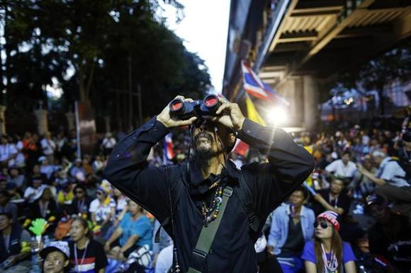 An anti-government protester uses binoculars to look at the national police headquarters where thousands are protesting at in Bangkok November 28, 2013. REUTERS/Damir Sagolj