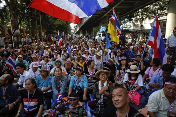 Anti-government protesters sit on the road outside the national police headquarters where they protest in Bangkok November 28, 2013. REUTERS-Damir Sagolj