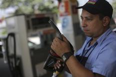 Frentista trabalha em um posto de combustível em São Paulo nesta sexta-feira. A Petrobras anunciou elevação média do preço da gasolina nas refinarias no país em 4 por cento e do diesel em 8 por cento. 29/11/2013 REUTERS/Nacho Doce