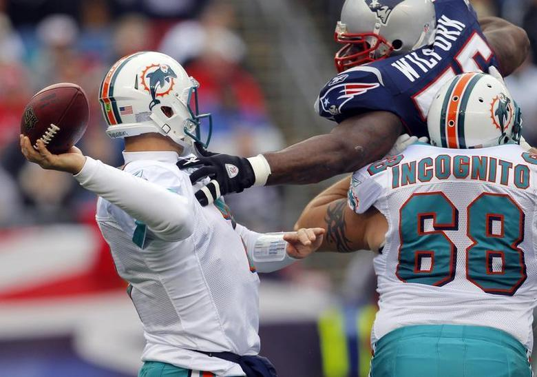 Miami Dolphins guard Richie Incognito (68) tries to stop New England Patriots defensive tackle Vince Wilfork (top R) from sacking Dolphins quarterback Chad Henne in the first quarter of their NFL football game in Foxborough, Massachusetts January 2, 2011. REUTERS/Brian Snyder