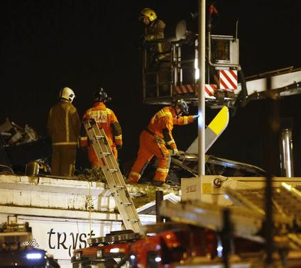 Rescue workers examine the wreckage of a police helicopter which crashed onto the roof of the Clutha Vaults pub in Glasgow, Scotland November 30, 2013. REUTERS-Russell Cheyne