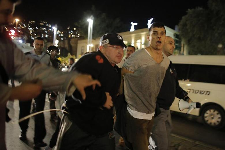Israeli police detain a protester during a demonstration showing solidarity with Bedouin Arabs who are against a government displacement plan for Bedouins in the Southern Negev desert in the northern city of Haifa November 30, 2013. REUTERS/Ammar Awad