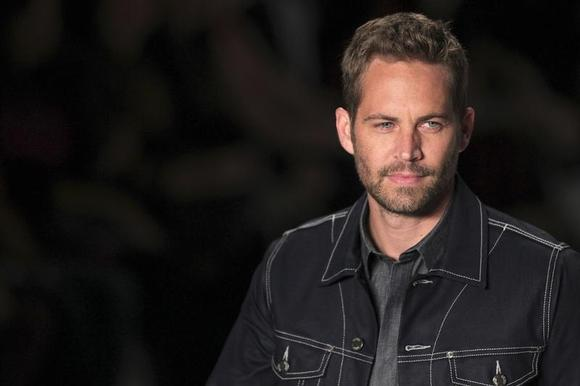 U.S. actor Paul Walker presents a creation from Colcci's 2013/2014 summer collection during Sao Paulo Fashion Week March 21, 2013. REUTERS/Filipe Carvalho/Files