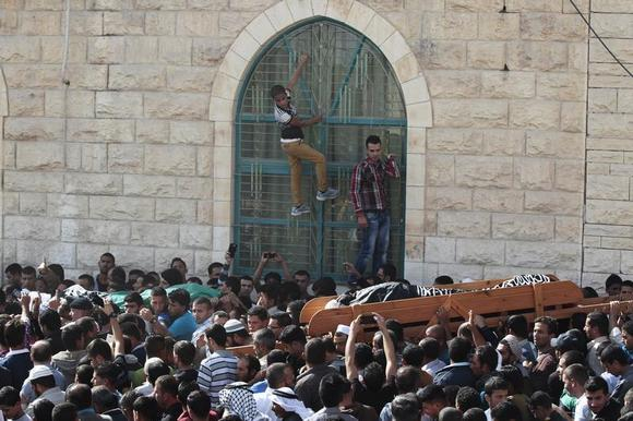 Boys hold onto window bars as the bodies of Palestinian Moussa Makhamra (R) and Khalid al-Najjar are carried during their funeral in the West Bank village of Yatta, near Hebron November 27, 2013. REUTERS/Ammar Awad