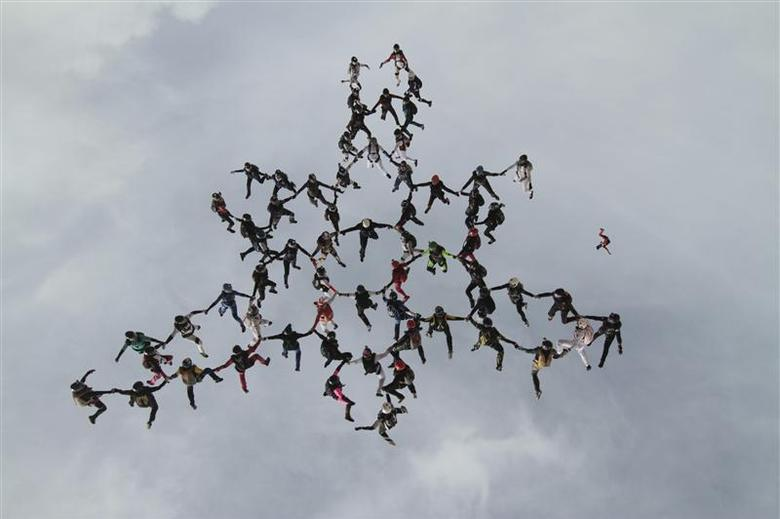 Sixty-three women from around the world are shown in this handout photo provided by the United States Parachute Association November 30, 2013 as they break the previous vertical formation skydiving record, leaping 18,000 feet from three aircrafts near Eloy, Arizona. REUTERS/Niklas Daniel/United States Parachute Association/Handout via Reuters