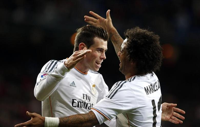 Real Madrid's Gareth Bale (L) celebrates his goal against Real Valladolid with teammate Marcelo during their Spanish First Division soccer match at Santiago Bernabeu stadium in Madrid November 30, 2013. REUTERS/Susana Vera