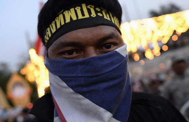 An anti-government protester, wearing a face mask in Thai national colours, rests as they tear down barricades during a demonstration outside Government House in Bangkok November 30, 2013. REUTERS/Dylan Martinez