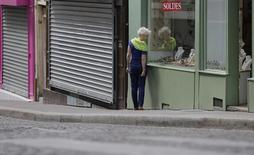 A woman makes her way past past opened and closed shops during a Sunday morning walk at the Butte Montmartre in Paris, July 28, 2013. REUTERS/Christian Hartmann