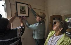 "Seminole Tribe member Edna Bowers (R), descendent of Polly Parker, looks on as fellow tribe member Willie Johns (L) and Florida Park Services Director Donald Forgione hang a photograph of Parker in a museum at Egmont Key State Park as part of a historic journey to retrace the ""Voyage of Tears"" in Egmont Key, Florida, December 1, 2013. REUTERS/Steve Nesius"