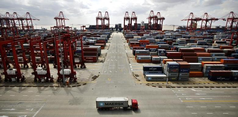 A container truck drives past the container area at the Yangshan Deep Water Port, part of the newly announced Shanghai Free Trade Zone, south of Shanghai September 26, 2013. REUTERS/Carlos Barria