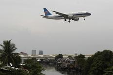 A China Southern Airlines aircraft flies over a slum before landing at Manila's International airport May 16, 2012. REUTERS/Romeo Ranoco