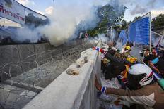 Участники антиправительственных выступлений укрываются за баррикадами в столкновении с пустившей слезоточивый газ полицией у здания правительства в Бангкоке 1 декабря 2013 года. Премьер-министр Таиланда Йинглак Чиннават в понедельник предложила оппозиции искать мирные пути выхода из политического кризиса, в ходе которого тысячи её противников вышли на улицы столицы с намерением свергнуть правительство. REUTERS/Athit Perawongmetha