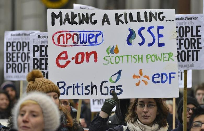 Demonstrators hold placards as they march to the headquarters of energy company npower during a protest against energy prices, London November 26, 2013. REUTERS/Toby Melville