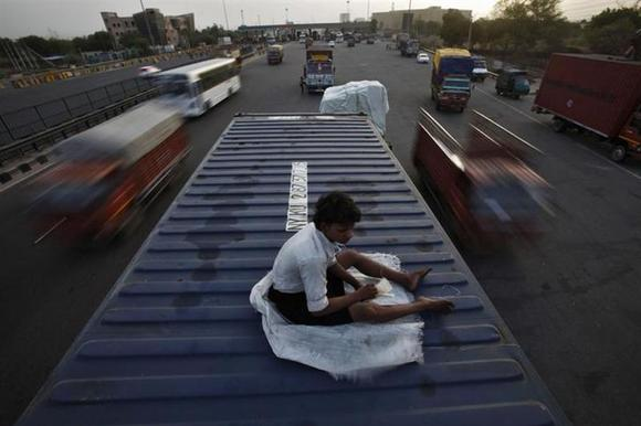 The helper of a driver rests on top of his parked truck along a busy highway on the outskirts of New Delhi June 15, 2012. REUTERS/Adnan Abidi/Files