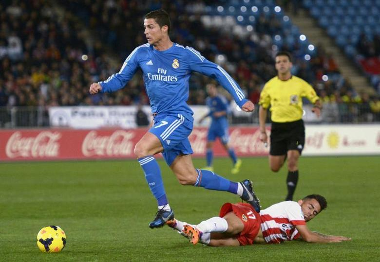 Real Madrid's Cristiano Ronaldo (top) is challenged by Almeria's Jesus Joaquin Fernandez ''Suso'' during their Spanish First Division soccer match at Juegos Mediterraneos stadium in Almeria November 23, 2013. REUTERS/Francisco Bonilla