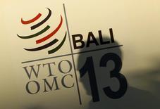 Um homem passa em frente ao logotipo da OMC em Bali. A crise é o estado natural das negociações mundiais sobre comércio. Mas esta semana será diferente. Ministros reunidos no balneário indonésio de Bali de terça a sexta-feira vão decidir o destino da Organização Mundial do Comércio (OMC), com dois possíveis desdobramentos: um acordo mundial de comércio, o primeiro desde que a OMC foi criada, em 1995, ou o fracasso que resultará no fim das conversações da rodada Doha de comércio e mergulhará a OMC na obsolescência. 02/12/2013 REUTERS/Edgar Su