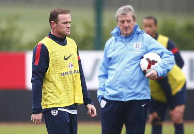 England national team soccer player Wayne Rooney (L) walks past manager Roy Hodgson during a team training session at Arsenal's training facility in London Colney, north of London, November 18, 2013. REUTERS/Andrew Winning