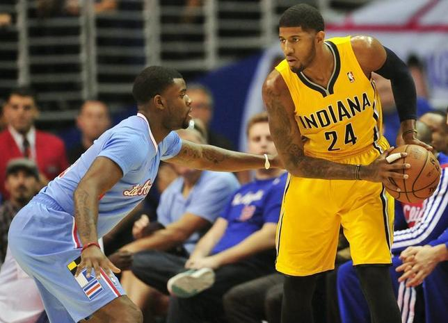 December 1, 2013; Los Angeles, CA, USA; Indiana Pacers small forward Paul George (24) controls the ball against the defense of Los Angeles Clippers shooting guard Reggie Bullock (25) during the first half at Staples Center. Gary A. Vasquez-USA TODAY Sports