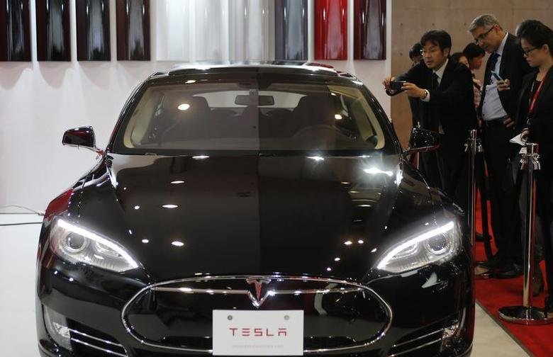 People take pictures of a Tesla Model S car, displayed at the 43rd Tokyo Motor Show November 20, 2013. REUTERS/Yuya Shino