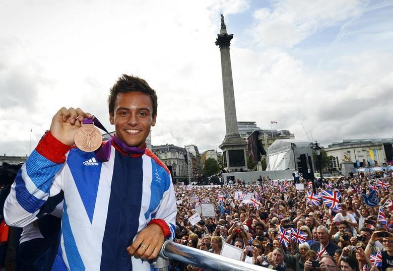 Diver Tom Daley holds his bronze medal during a parade through London September 10, 2012. REUTERS/David Davies/Pool