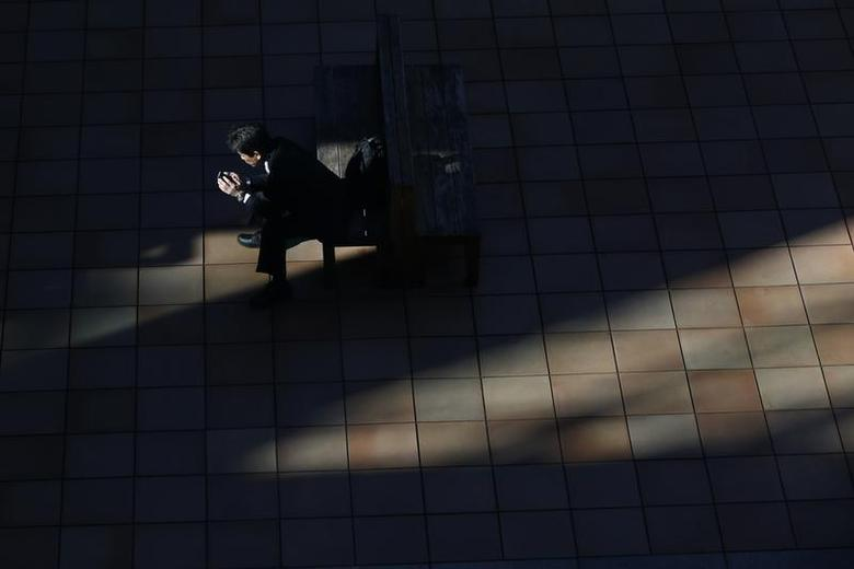 A man uses a smartphone on a street in Tokyo November 21, 2013. REUTERS/Issei Kato