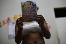 Vanessa, 13, who was picked up by the police on the streets, poses with a DVD cover at a shelter for girls who have faced sexual violence or sexual commercial exploitation, where she was sheltered after undergoing treatment for crack cocaine abuse, in Fortaleza November 1, 2013. REUTERS/Ricardo Moraes