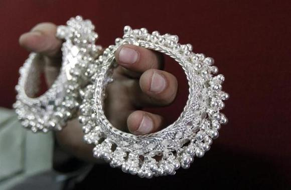 A silver trader displays silver ornaments inside his shop in Ahmedabad April 27, 2011. REUTERS/Amit Dave/Files