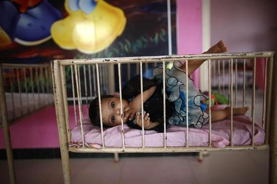 A baby girl is seen lying in a cradle inside the Life Line Trust orphanage in Salem in Tamil Nadu June 20, 2013. Thomson Reuters Foundation-Mansi Thapliyal-Files