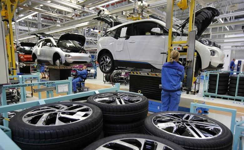 A worker mounts a tyre at the serial production BMW i3 electric car in the BMW factory in Leipzig September 18, 2013. REUTERS/Fabrizio Bensch