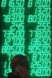 Женщина с мобильным в руках входит в обменный пункт в Киеве 16 октября 2013 года. Минфин охваченной массовыми протестами Украины во вторник пообещал кредиторам своевременно и в полном объёме платить по суверенным долгам, выступив с успокаивающим заявлением вслед за Нацбанком, который призвал к спокойствию вкладчиков. REUTERS/Gleb Garanich