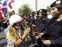 Участница антиправительственных выступлений вручает розы полицейским на акции протеста у штаб-квартиры МВД в Бангкоке 3 декабря 2013 года. Правительство Таиланда приказало полиции прекратить омрачённое насилием противостояние с требующими отставки премьер-министра демонстрантами, но лидер оппозиции сказал, что борьба продолжится. REUTERS/Kerek Wongsa