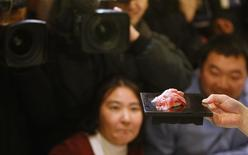 Guests look at tuna sushi made from a 222 kg (489 lbs) bluefin tuna at a sushi restaurant outside Tsukiji fish market in Tokyo January 5, 2013. REUTERS/Toru Hanai